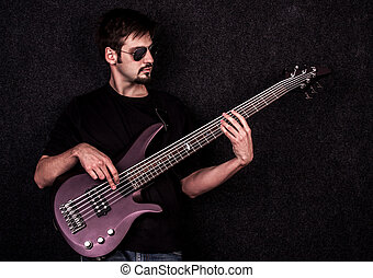 Man playing on bass guitar, shot in studio.