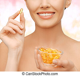 beautiful woman with omega 3 vitamins - healthcare and...