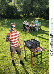 Barbecue chef - Confident looking man standing with kitchen...