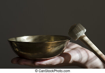A Tibetan singing bowl being played with a baton. - A...