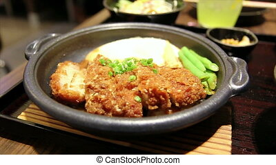 japanese food fry pork tongkatsu with egg on hot metal plate