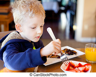 child eating breakfast - cute positive boy eating...