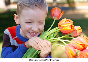spring time - little laughing boy holding flowers at spring...