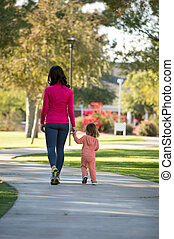 Beautiful mother and daughter walking in the neighborhood -...