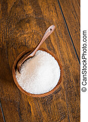 White sugar in a wooden bowl with a spoon.