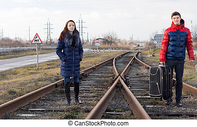 Young couple waiting for the train on the tracks