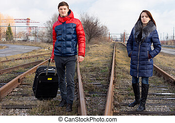 Young couple waiting on the railway tracks with a packed...