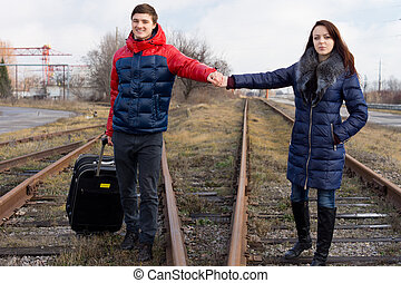 Young couple walking along a railway line