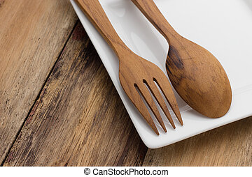 Plate with spoon and fork on wood table