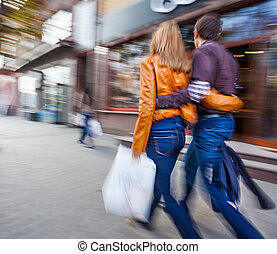 Man and woman walking down the street hugging - Man in jeans...