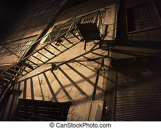 Spooky back yard with fire escape casting shadow on wall