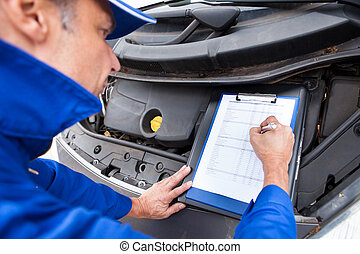 Mechanic Maintaining Car Records - Close-up Of A Mature...
