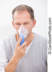 Man Doing Inhalation Through Oxygen Mask At Home