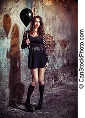 Strange young girl holding black balloon - A strange young...