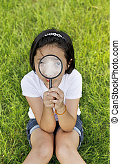 Asian little girl holding a magnifying glass in outdoor -...