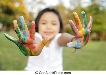 Asian little girl with hands painted in colorful paints