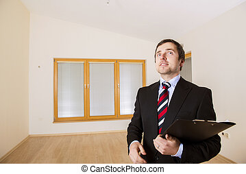 Real Estate Agent is standing in new empty house
