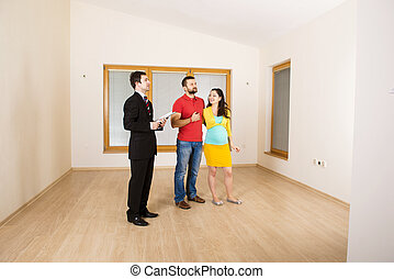 Real Estate Agent with couple - Real Estate Agent with young...