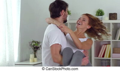Happy Couple - Slow-motion of a happy guy carrying his...