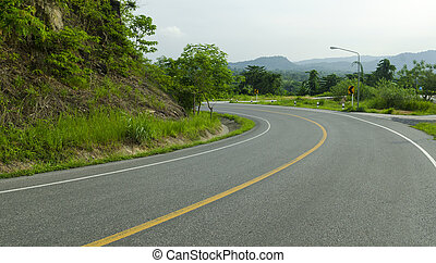 Asphalt road sharp curve along with tropical forest zigzag...