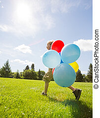 Boy With Helium Balloons Walking In Park - Full length side...