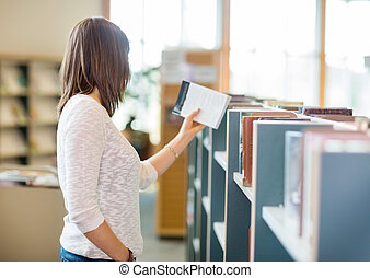 Student Reading Book In Library - Side view of young college...