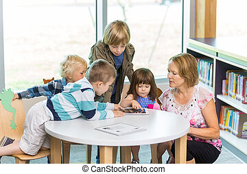 Teacher With Students Using Digital Tablets In Library -...
