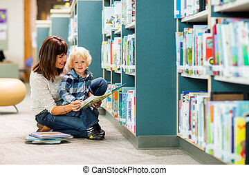Boy With Teacher Reading Book In Library - Portrait of boy...
