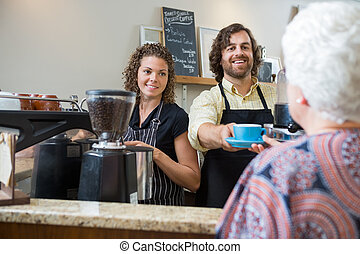 Cafe Owners Serving Coffee To Woman At Counter - Smiling...