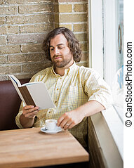 Man With Coffee Cup Reading Book In Cafe - Mid adult man...