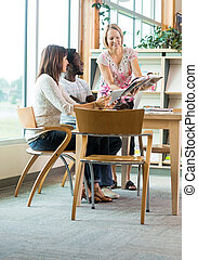 Librarian Assisting Students In Library