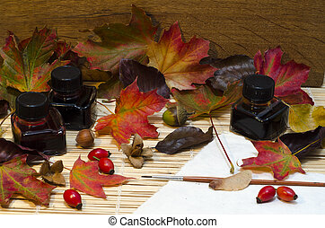 Arrangement of autumn leaves, nuts and berries, bottles of...