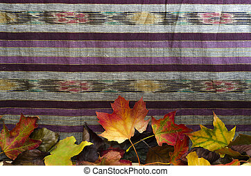 A cloth background decorated with colourful autumn leaves...