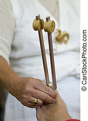 Practitioner giving healing tuning fork treatment - Close up...