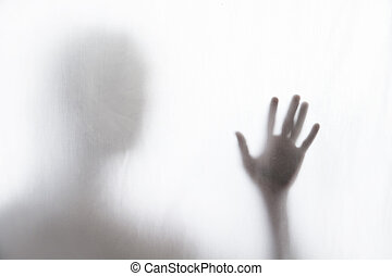 Shadow of man standing behind thin fabric