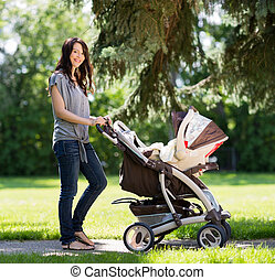 Beautiful Woman Pushing Baby Carriage In Park - Portrait of...