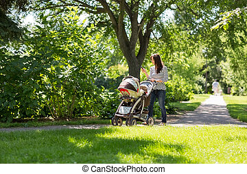 Mother Pushing Baby Carriage In Park - Full length of young...