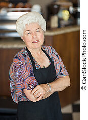 Confident Senior Owner Standing In Coffee shop - Portrait of...
