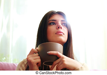 Young pensive woman with cup of coffee looking away