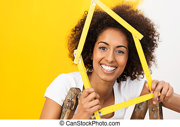 Excited African American woman in her new home holding up a...