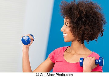 Happy beautiful woman exercising in the gym