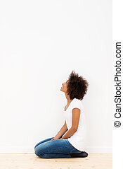 Woman kneeling looking at a white wall - African American...