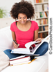 Woman studying hard and taking notes - African American...