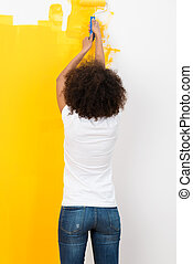Woman with an afro hairstyle painting a wall bright orange...