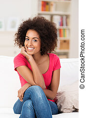 Beautiful African American with an afro hairstyle relaxing...