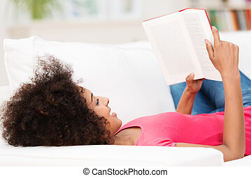 Woman laying on her back on the sofa, reading