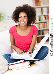 Cheerful female student sitting on the sofa
