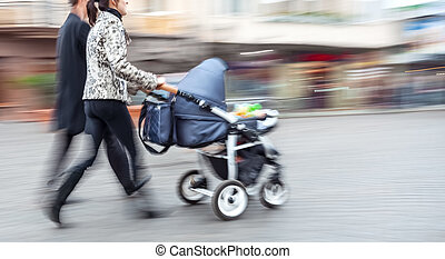 Young family with small children and a pram walking down the...