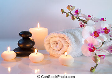preparation for massage with towels, stones, and orchid