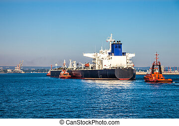 Tugboats and tanker - A huge oil tanker and tugboats at...